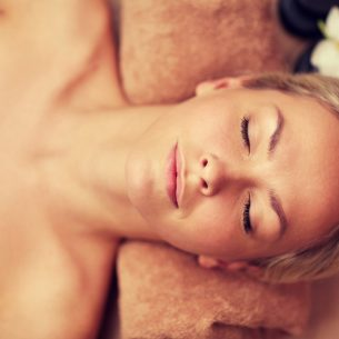 close up of smiling young woman lying in spa